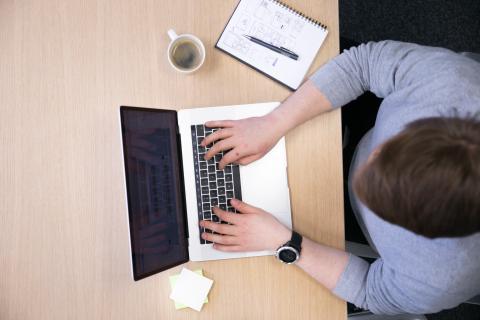 Mies istuu kannettavan tietokoneen edessä pöydän ääressä.
